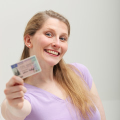Smiling blonde woman showing her ID card