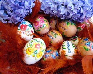 Easter eggs in a basket with colorful feathers