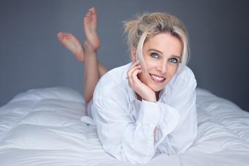 belle blonde sourie sur couette
