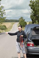 Woman waiting for help near  car