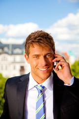 attraktiver geschäftsmann telefoniert mit smartphone