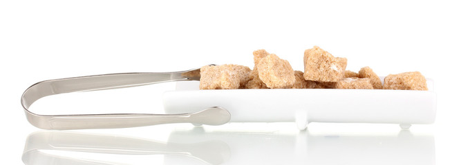 Lump brown cane sugar cubes on plate isolated on white