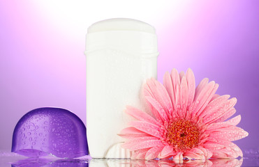 deodorant with flower on purple background