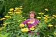 Seniorin im Garten mit Sonnenauge