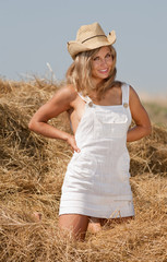 Long-haired blond girl in haystack