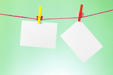 photo paper hanging on the clothesline on light green background