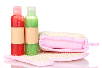 Bottles with scrub and sponges isolated on white