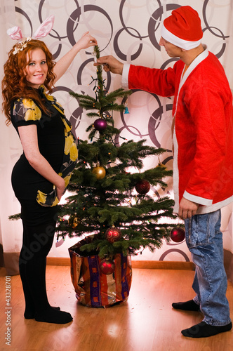 Happy couple decorating Christmas tree with baubles