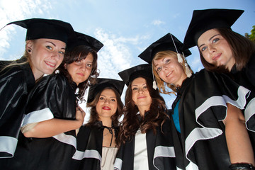 A group of girls in gowns of graduates and academic caps