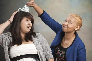 Woman putting tiara on friend's head