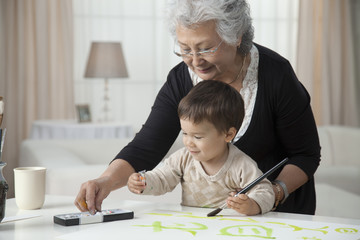 Grandmother teaching grandson to paint