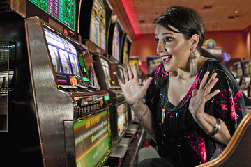 Excited Caucasian woman playing slot machines in casino