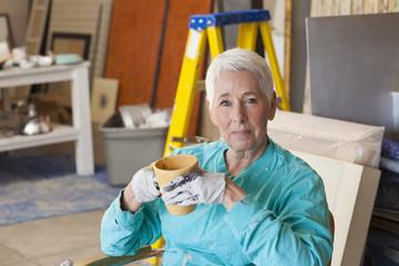 Caucasian artist drinking coffee in studio