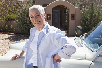 Caucasian woman leaning on car in driveway