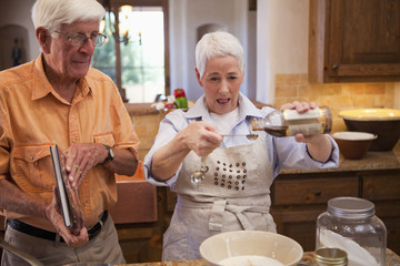 Caucasian couple cooking together in kitchen