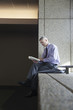 Caucasian businessman reading book on office ledge