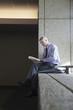 Caucasian businessman reading book on office ledge