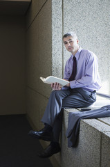 Caucasian businessman reading book on office windowsill