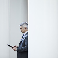 Caucasian businessman using digital tablet in corridor