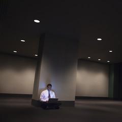 African American businessman sitting on floor using laptop