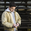 Caucasian worker using cell phone in factory