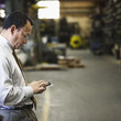 Hispanic foreman using cell phone in factory