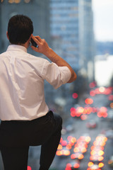 Caucasian businessman talking on cell phone and looking at traffic