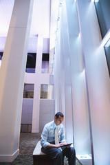 Hispanic businessman using digital tablet in lobby