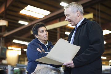 Foreman talking to worker in factory