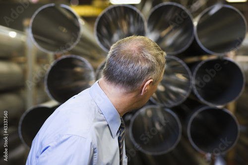 Caucasian foreman looking at pipes in factory