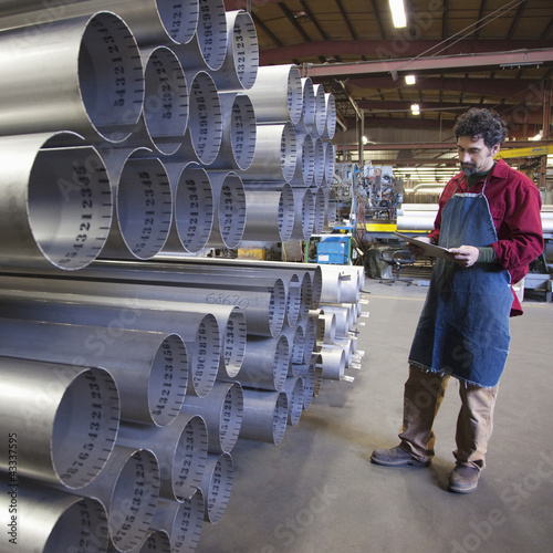 Mixed race worker standing near pipes in factory