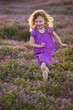 Caucasian girl running through field of flowers