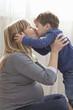 Pregnant Caucasian mother kissing son