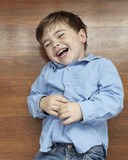 Laughing Caucasian boy laying on floor