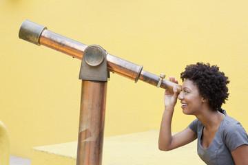 African American woman looking through telescope