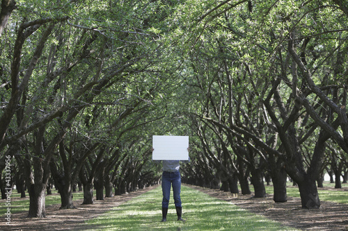 Caucasian woman holding blank placard underneath trees