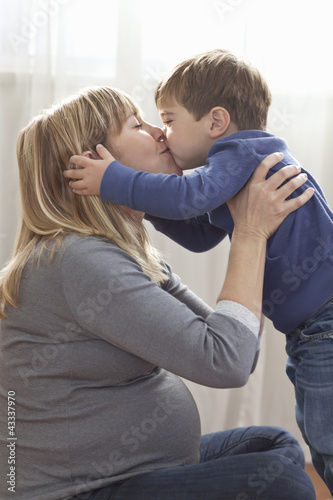 Pregnant Caucasian mother kissing son