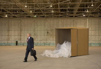Caucasian businessman walking away from large box in warehouse