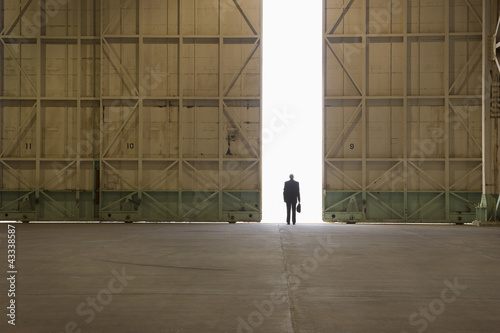 Caucasian businessman standing in warehouse doorway