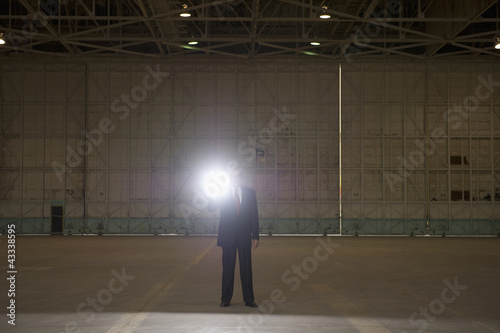 Caucasian businessman using flashlight in warehouse