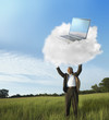 Black businessman holding laptop on cloud in field