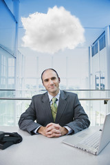 Caucasian businessman sitting at desk with cloud over his head