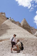 Hispanic couple hiking together in canyon