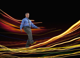 Mixed race businessman walking on glowing lines