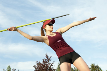 Caucasian athlete throwing javelin