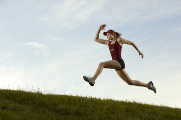 Caucasian runner running in field