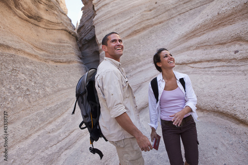 Hispanic couple hiking together in canyon