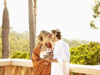 Glamorous Caucasian couple drinking red wine and kissing outdoors