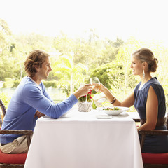 Glamorous Caucasian couple toasting in restaurant
