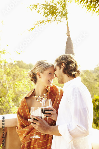 Glamorous Caucasian couple drinking red wine outdoors